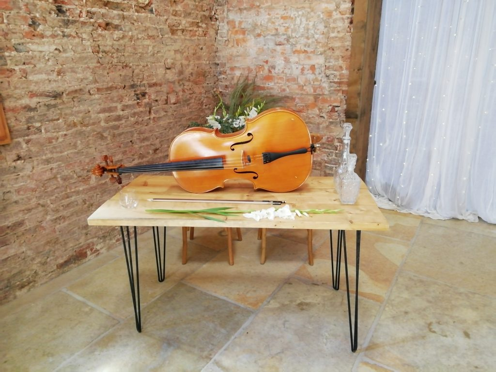 Cello and wedding flowers on a table in the ceremony space at The Barns, East Yorkshire where the India Rose Strings trio performed for a wedding