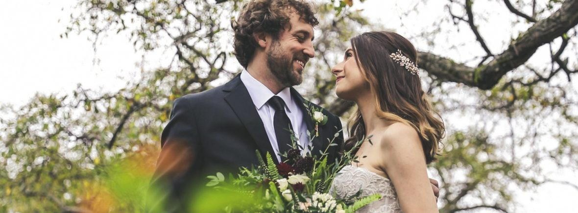 Bride and groom smile at each other surrounded by trees.